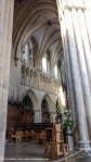 from edge of the south side of the nave looking across the crossing into the north choir. Here you can just see lancet windows at the clerestory level windows and a blind arcade with thin columns at gallery level. Also the ornate choir stalls