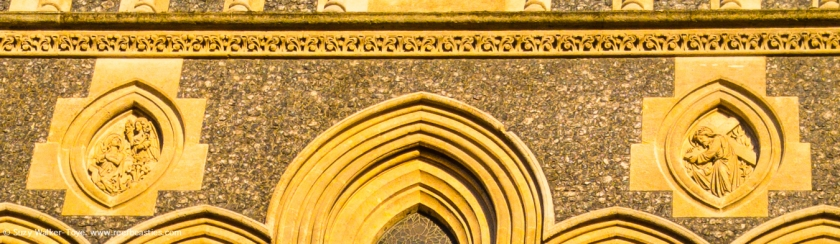 Detail of the last picture, of the exterior view of the West end of the nave. This shows two pointed medallion moldings with relgious scenes in them above the arched windows and a strip of arabesque molding along the top.